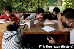 Dimas Anwar Saputra, siswi SMP berusia 15 tahun, mengenakan masker pelindung berwarna merah, belajar bersama siswa lain menggunakan akses internet wifi gratis.(Foto: REUTERS/Willy Kurniawan)