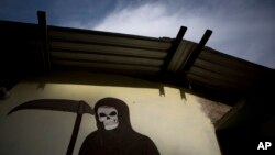 FILE - A mural of La Santa Muerte, or Saint Death, decorates the wall of a community center in Colonias, Michoacan state, Mexico, where vigilantes met with families after a shooting, Jan. 8, 2015.
