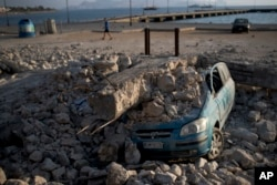 A man walks past a car crushed under rubble near the port of the Greek island of Kos, July 22, 2017.