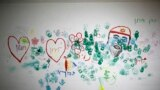 """A wall decorated with paintings by children are seen in a bomb shelter in the Israeli southern city of Ashkelon, July 31, 2014. The words in Hebrew read, """"Protective Edge."""""""