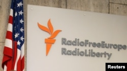 FILE - A sign for Radio Free Europe/Radio Liberty is seen next to a U.S. flag at the U.S.-funded broadcaster's headquarters in central Prague, Czech Republic, Oct. 5, 2005.