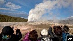 En esta foto de archivo de 2011 turistas fotografían la erupción de aguas termales Old Faithful, en el Parque Nacional Yellowstone.