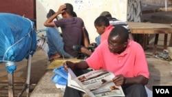Un homme en pleine lecture de son journal à Westfield, à Banjul, en Gambie, le 7 juin 2017. (S.Christensen/VOA)