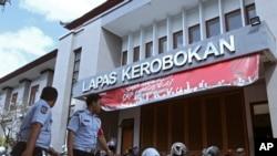 Para petugas penjara berjalan di depan pintu masuk gedung penjara Kerobokan, Bali, 19 Juni 2017. (AP Photo/Firdia Lisnawati).