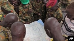 FILE - Soldiers from the Sudan People's Liberation Army examine a map at the front-line position in Pana Kuach, Unity State, South Sudan, May 11, 2012.