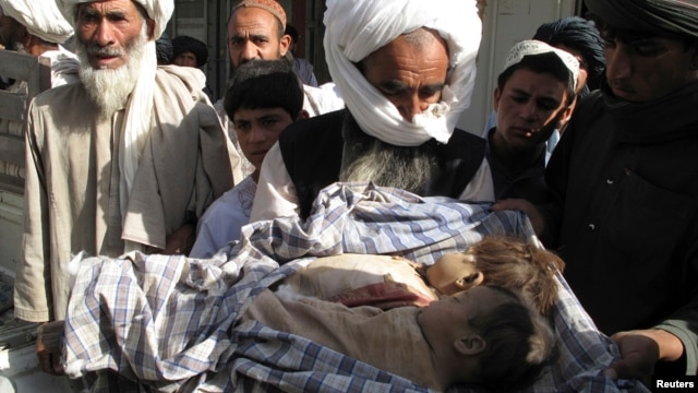 Man holds bodies of two children killed in counter-insurgency airstrike called in by US-NATO led troops, Helmand, Afghanistan, May 29, 2011.