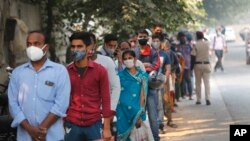 In this Nov. 6, 2020, file photo, people queue to get tested for COVID-19 as a thick quilt of smog lingers over New Delhi, India. (AP Photo/Manish Swarup, File)