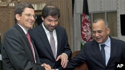Pakistan's Foreign Secretary Salman Bashir, right, joins hands with Afghanistan Deputy Foreign Minister Jaweed Ludin, center, and US Special Representative for Afghanistan and Pakistan Marc Grossman prior their joint news conference at the Foreign Office