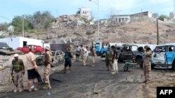 Pasukan Yaman dan warga berkumpul di lokasi ledakan bom bunuh diri yang menaget kepala polisi di pangkalan militer yang didukung pemerintah Saudi di kota Aden, Yaman (28/4).