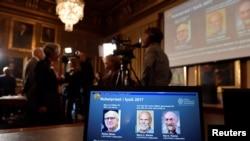 Os nomes de Rainer Weiss, Barry C. Barish e Kip S. Thorne durante a divulgação de vencedores em Estocolmo.