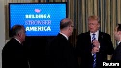 도널드 트럼프 미국 대통령(오른쪽)이 12일 백악관에서 사회기반시설 확충 방안을 토론하는 회의를 열고 참석자들과 대화하고 있다.