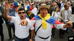 FILE - Opponents of government peace talks with FARC guerrillas shout slogans during a march in Bogota, Colombia, Dec. 13, 2014.