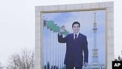 A woman walks past a board displaying a portrait of Turkmenistan's President Gurbanguly Berdimuhamedov in Ashgabat, February 10, 2012.