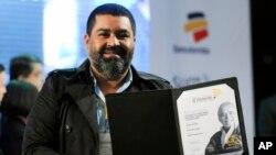 """Esteban Felix, fotografer Associated Press asal Peru yang ditempatkan di Peru, menunjukkan penghargaan internasional """"Gabriel García Márquez"""" untuk karya fotonya seusaia upacara penyerahan penghargaan di Medellin, Kolombia (20/11)."""