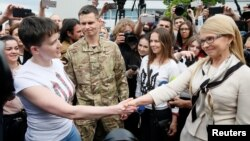Ukrainian servicewoman Nadiya Savchenko shakes hands with Ukrainian former Prime Minister and leader of Batkivshchyna (Fatherland) party Yulia Tymoshenko at Boryspil International airport outside Kyiv, May 25, 2016.