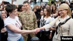 우크라이나 육군 헬리콥터 조종사 나디야 사브첸코(왼쪽)가 25일(현지시간) 수도 키에프에 도착한 직후 공항에서 우크라이나 전 총리인 율리아 티모셴코 조국당 대표와 악수를 나누고 있다.