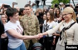 FILE - Ukrainian pilot Nadiya Savchenko, left, shakes hands with Fatherland party leader Yulia Tymoshenko at Boryspil International Airport outside Kyiv, Ukraine, May 25, 2016.