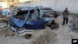 Seorang warga Irak memeriksa kendaraan yang hancur akibat serangan bom di Baghdad, Senin (16/12).