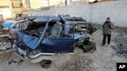 一名男子在檢視12月16日在巴格達附近發生的汽車炸彈襲擊現場