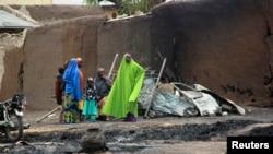 Wasu mata da yara tsayer a jikin wani gidan da ya kone a Baga, Jihar Borno