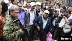 Un miembro de las FARC es rodeado por un grupo de índigenas y periodistas en uno de los accesos a Toribío, en la provincia del Cauca, donde los índigenas han exigido que se retiren los elementos armados de la guerrilla y el ejército.