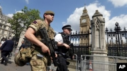 "FILE - A member of the army joins police officers on patrol in Westminster, London, May 24, 2017. Britons find armed troops at vital locations as the country's terror threat level remains at ""severe"" - the second highest on Britain's five-tier scale."