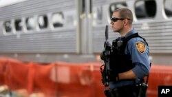 Tư liệu- Một nhân viên cảnh sát đứng gác gần một đoàn tàu tại ga Hoboken, bang New Jersey.