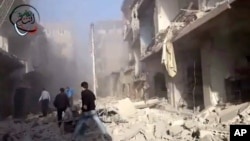In this photo taken from video obtained from the Shaam News Network, Syrian men run to aid injured people in the aftermath of a strike by Syrian government warplanes on a neighborhood south of Damascus, Monday, Jan. 14, 2013.