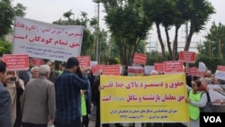 Dozens of Iranian education activists stage a protest outside the government's planning and budget office in Tehran, May 10, 2018. The protesters held signs calling for teachers to be paid at least more than Iran's minimum wage (yellow sign, right) and for education to remain free for all Iranians (white sign, left). (Activist photo sent to VOA Persian)