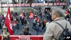 A man looks at demonstrators marching during a protest in Paris as part of the 7th day of actions against the pension reform law, 28 Oct 2010