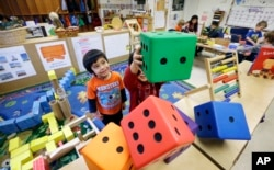 FILE - In this photo taken Friday, Feb. 12, 2016, Daniel O'Donnell, left, looks on as William Hayden sends large blocks flying at the Creative Kids Learning Center, a school that focuses on pre-kindergarten in Seattle. (AP Photo/Elaine Thompson)