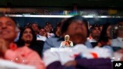 Prime Minister Narendra Modi of India is reflected in a glass barrier as he gives a speech during a reception by the Indian community in honor of his visit to the United States at Madison Square Garden, Sunday, Sept. 28, 2014.