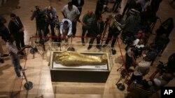Para jurnalis berkumpul di sekitar peti mati emas yang pernah digunakan untuk menyimpan mumi Nedjemankh, seorang imam di Zaman Ptolemeus sekitar 2.000 tahun yang lalu, di Museum Nasional Peradaban Mesir, di Kairo, Mesir, Selasa, 1 Oktober, 2019.