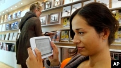 FILE - A woman reads an e-book at a book fair in Frankfurt, central Germany.