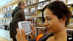 FILE - A woman reads an E-Book at the Book Fair in Frankfurt, central Germany.