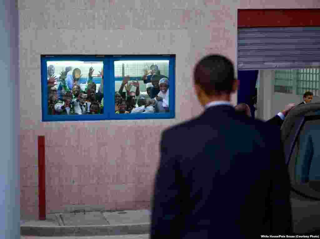 Obama retourne à sa limousine alors que des employés de l'hôtel le saluent pour attirer son attention, Ghana, le 11 juillet 2009. (White House/Pete Souza)