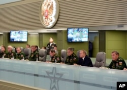 Russian President Vladimir Putin, second right, flanked by Defense Minister Sergei Shoigu, third right, and Chief of the General Staff of the Russian Armed Forces Valery Gerasimov, right, attends a meeting on Russian airspace forces' activities in Syria.