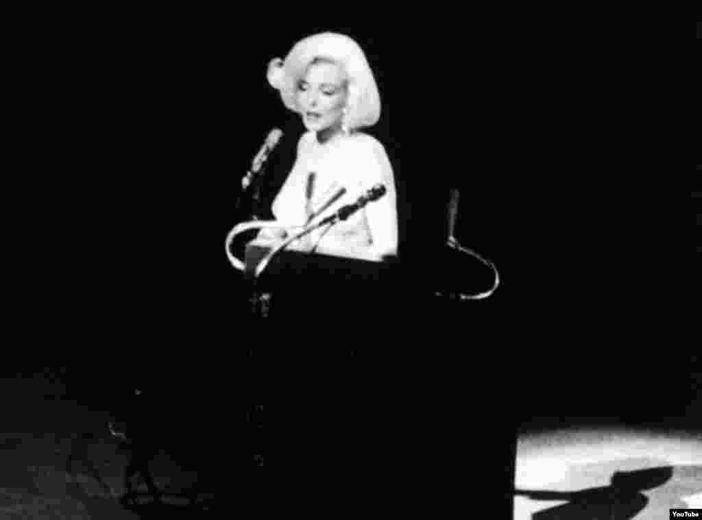 Nữ minh tinh Marilyn Monroe xuất hiện trên khấu lễ trao giải Oscar năm 1962 và hát chúc mừng sinh nhật Tổng thống John F. Kennedy với lời bài hát do cô viết lại. Sự kiện này càng khơi lên thêm những đồn đoán về mối quan hệ giữa cô và vị tổng thống. Đây cũng là lần xuất hiện cuối cùng của Marilyn Monroe trước công chúng trước khi qua đời vài tháng sau đó. (Ảnh tư liệu).