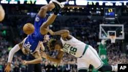 A player for the Philadelphia 76ers falls as he tries to block a shot by Boston Celtics' player in this 2017 NBA basketball game. (AP Photo/Elise Amendola)