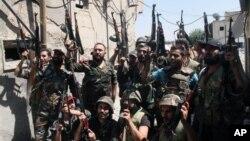 시리아 정부군이 14일 다마쿠스 근교에서 반군과의 전투 후 환호하고 있다.