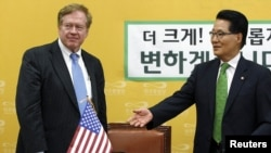 Park Ji-won (R), floor leader of South Korea's main opposition Democratic United Party, greets Robert King, U.S. envoy on human rights in North Korea, at the Park's office at the national assembly in Seoul, June 13, 2012.
