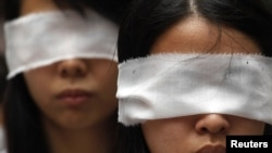 Protesters cover their eyes with white ribbons to symbolize mourning, as a protest to urge the Chinese authorities to carry out a proper investigation into the death of dissident Li Wangyang in Hong Kong June 10, 2012.