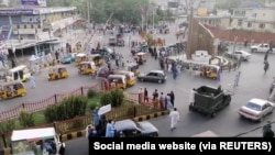 Taliban militants waving a Taliban flag on the back of a pickup truck drive past a crowded street at Pashtunistan Square area in Jalalabad, Afghanistan in this still image taken from social media video uploaded on August 15, 2021. Social media website/via REUTERS THIS IMAGE HAS B