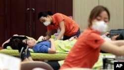 Nurses wear masks as a precaution against the MERS (Middle East Respiratory Syndrome) as they take blood donations from officials at Dongdaemun District Office in Seoul, South Korea, Thursday, June 18, 2015.