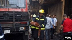 A fireman folds a fire extinguisher tube after his truck runs out of water in a busy, commercial area downtown Cairo on May 11, 2016. (VOA /Hamada Elrasam)