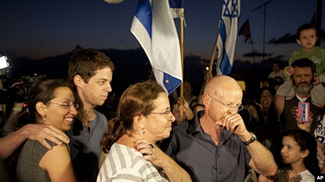 Noam and Aviv Schalit, right, Yoel Schalit and Yaara Winkler, parents and brother of captured Israeli soldier Gilad Schalit are welcomed by family and friends to their home in Mitzpe Hila, northern Israel, October 12, 2011.
