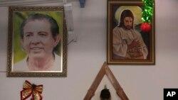 زنی در حال عبادت و میان دو تصویر از عیسی مسیح (راست) و ژائو تیشریا د فاریا (چپ)