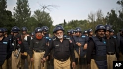Pakistani police officers stand guard near the Parliament building after tens of thousands of protesters entered Islamabad's high-security Red Zone the night before, five days after arriving in the capital from the eastern city of Lahore in convoys, in Is