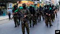 FILE - Palestinian masked militants of Izzedine al-Qassam Brigades, a military wing of Hamas. According to Palestinian law, all executions must be approved by Palestinian president Mahmoud Abbas.