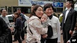 新当选的香港特首林郑月娥(前右一)3月27日在香港与当地居民合影。